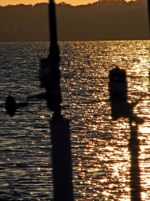 Fishing Poles Against Sunrise Reflection